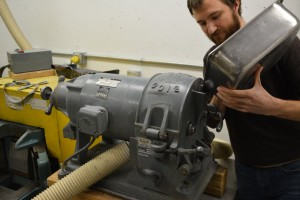 [Photo: Nathan Andersen  introduces a granular sample into the disk mill for crushing.]